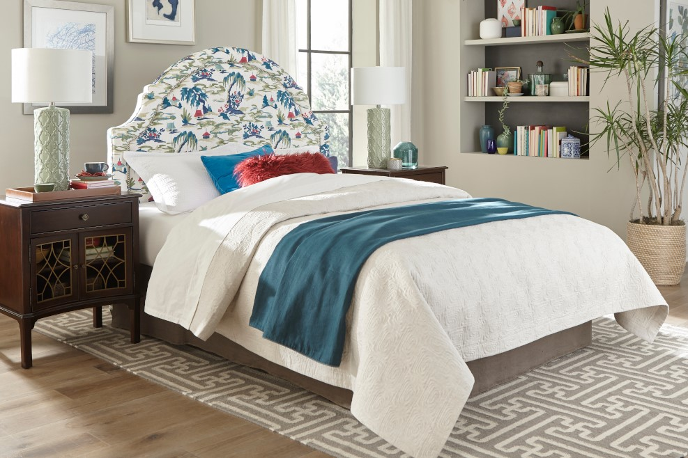 In your Chattanooga interior design efforts, allow summer to splash across your bedroom with the perfect balance of white and layers of color seen here.